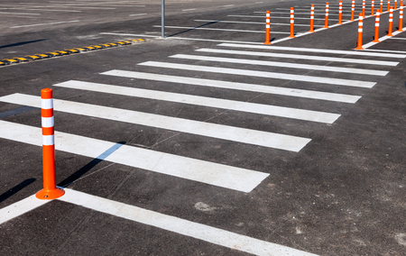 White traffic markings with a pedestrian crossing on a gray asphalt parking lot photo