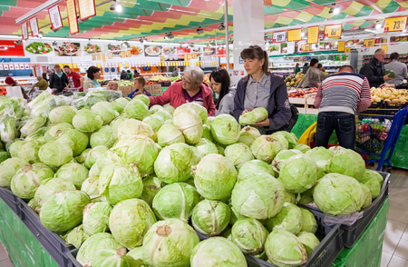 SAMARA, RUSSIA - SEPTEMBER 23, 2014: Buyers select fresh vegetables in supermarket Magnit. Russias largest retailer