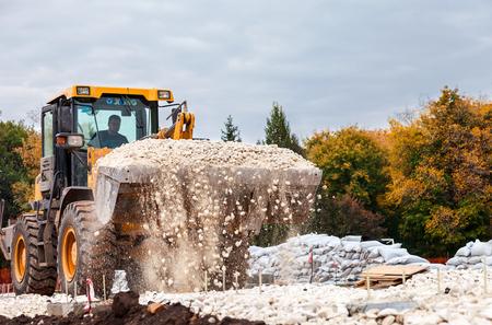 SAMARA, RUSSIA - SEPTEMBER 28, 2014: Heavy bulldozer loading and moving gravel on road construction site
