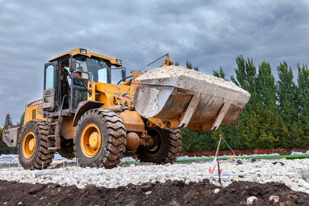 aggregates: SAMARA, RUSSIA - SEPTEMBER 28, 2014: Heavy bulldozer loading and moving gravel on road construction site