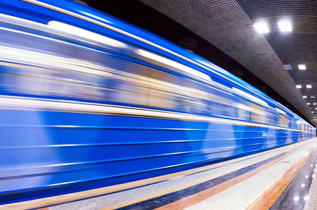 Blue subway train in motion at the station photo