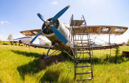 aerodrome: SAMARA, RUSSIA - MAY 25, 2014: Old russian aircraft An-2 at an abandoned aerodrome in summertime. The Antonov An-2 is a Soviet mass-produced single-engine biplane