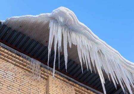 snow drops: Large icicles hanging on the roof of the house in springtime Stock Photo