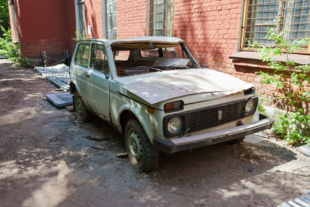 SAMARA, RUSSIA - MAY 22, 2013: Abandoned broken russian automobile Lada at the abandoned town in summertime