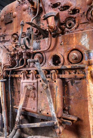 Old steam train engine with rust and damage photo