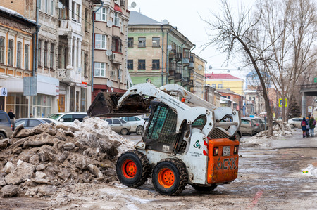 SAMARA, RUSSIA - MARCH 9, 2015: Snow plough cleaning the streets of city from snow and ice after the heavy snowfall