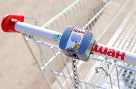 unites: SAMARA, RUSSIA - MARCH 14, 2015: Empty red shopping cart Auchan store. French distribution network Auchan unites more than 1300 shops