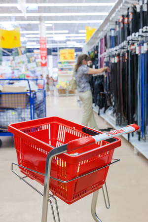 unites: SAMARA, RUSSIA - AUGUST 30, 2014: Empty red shopping cart Auchan store. French distribution network Auchan unites more than 1300 shops Editorial