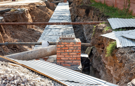 struts: SAMARA, RUSSIA - SEPTEMBER 13, 2014: Repair of underground heating.  Insulated pipes to connect a new buildings on heat system