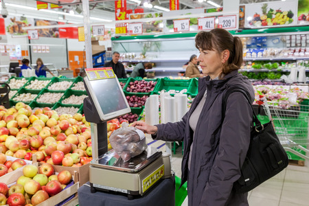 produce departments: SAMARA, RUSSIA - OCTOBER 10, 2014: Young woman weighing potatoes on electronic scales in produce department of the Magnit store. Russias largest retailer