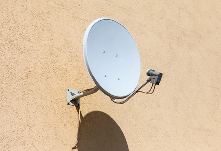 telecast: Satellite dish mounted on the wall of house