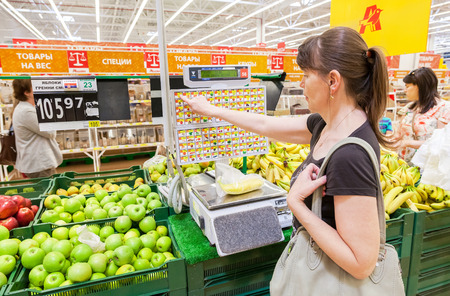 produce departments: SAMARA, RUSSIA - JUNE 13, 2015: Young woman weighing bananas on electronic scales in produce department of the Auchan store Editorial