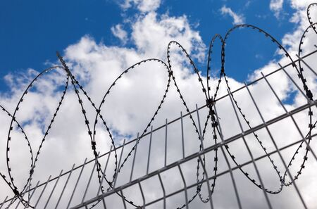 repression: Barbed wire on blue sky background