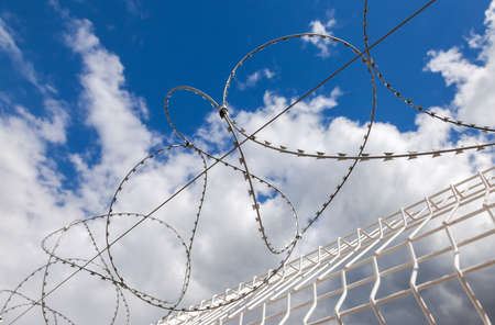 totalitarian: Barbed wire on blue sky background