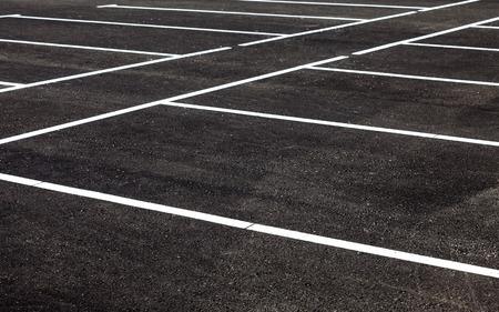 Weiße Verkehrsmarkierungen auf einem grauen Asphalt-Parkplatz Standard-Bild - 44929998