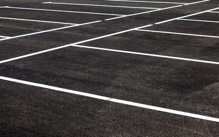 White traffic markings on a gray asphalt parking lot