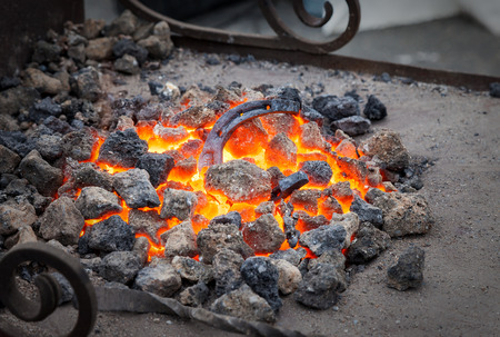 smithery: Blacksmithing, metal horseshoe is heated in the forge on coals Stock Photo