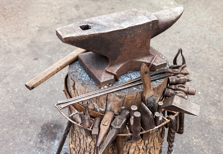 ancient blacksmith: Old anvil with blacksmith tools on the outdoors Stock Photo