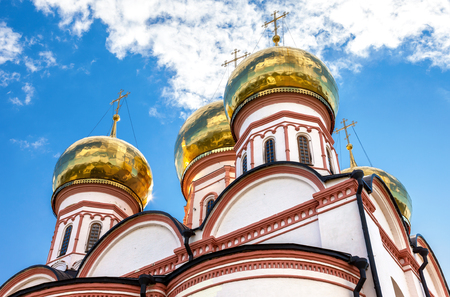 Golden domes of Russian orthodox church in Valday monastery against the blue sky