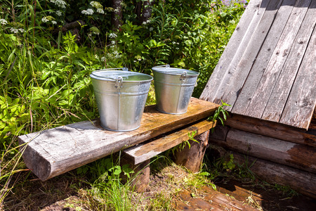 sump: Metal buckets with cool water standing on a bench at the village water well