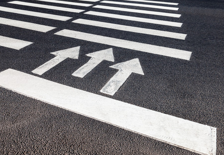 Zebra crossing with white marking lines and direction of motion on asphalt Stock Photo