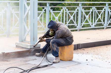 sandblasting: Worker in protective clothes cleans the metal structures sandblasting tool Stock Photo