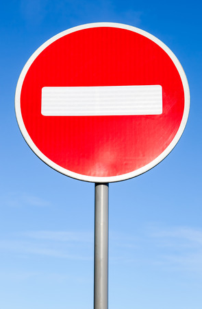 red sign: Stop sign against the blue sky background