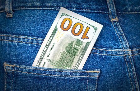 one hundred dollars: One hundred dollars bill sticking out of the back jeans pocket Stock Photo