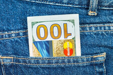 mastercard: SAMARA, RUSSIA - DECEMBER 23, 2015: Credit card MasterCard with US dollars sticking out of the back jeans pocket
