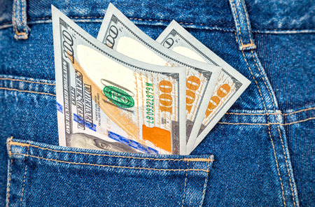 u s: Banknotes of one hundred U. S. dollars bill sticking out of the back jeans pocket