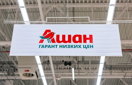low prices: SAMARA, RUSSIA - JANUARY 17, 2016: Auchan trade mark. Text in Russian: Auchan - guarantee low prices. French distribution network Auchan united more than 1300 shops