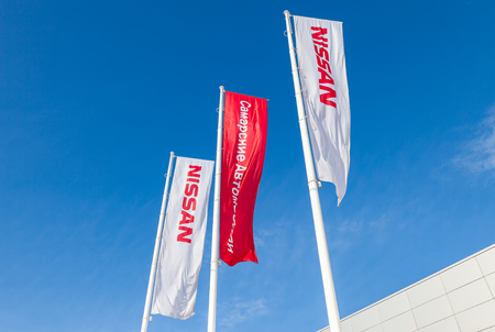 automaker: SAMARA, RUSSIA - APRIL 27, 2014: The flags of official dealer Nissan over blue sky. Nissan is a Japanese multinational automaker headquartered in Nishi-ku, Yokohama, Japan