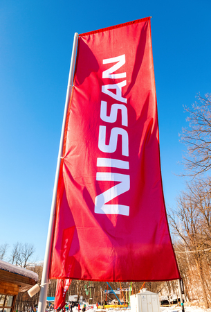 automaker: SAMARA, RUSSIA - JANUARY 14, 2016: Dealership flag Nissan over blue sky. Nissan is a Japanese multinational automaker