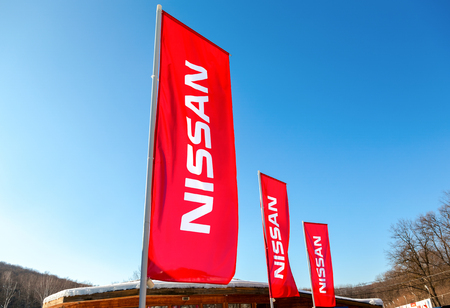 automaker: SAMARA, RUSSIA - FEBRUARY 14, 2016: Dealership flags Nissan over blue sky in sunny day. Nissan is a Japanese multinational automaker