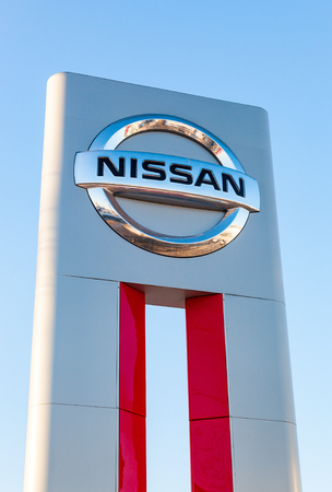 automaker: SAMARA, RUSSIA - FEBRUARY 13, 2016: Official dealership sign of Nissan against blue sky. Nissan is a Japanese multinational automaker Editorial