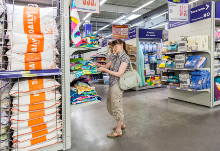 diversified: SAMARA, RUSSIA - MAY 31, 2015: Young woman choosing bedclothes at shopping in hypermarket METRO. Metro Group is a German global diversified retail group