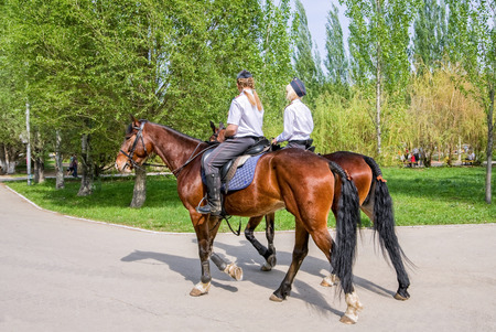 girl with horse: SAMARA, RUSSIA - MAY 9, 2015: Female mounted police on horse back in the city Park