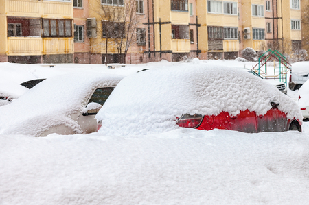 inclement: SAMARA, RUSSIA - FEBRUARY 28, 2016: Vehicles covered with snow in the winter blizzard in the parking lot Editorial