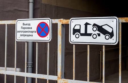 parking is prohibited: Traffic sign prohibiting parking mounted on metal gate. Evacuation on tow truck. Text in Russian: Parking of vehicles is prohibited Stock Photo