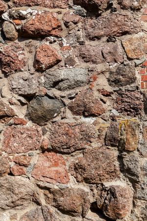 crannied: Rough natural old stone wall as background Stock Photo