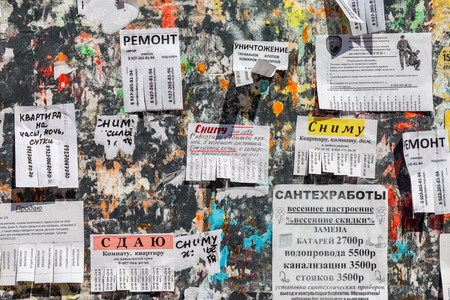 old poster: SAMARA, RUSSIA - APRIL 10, 2016: Dirty bulletin board filled with paper notices on russian language Editorial