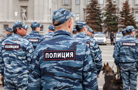 police unit: SAMARA, RUSSIA - APRIL 20, 2016: Russian police unit in uniform with police dogs on the Kuibyshev square in spring day. Text in russian: Police Editorial