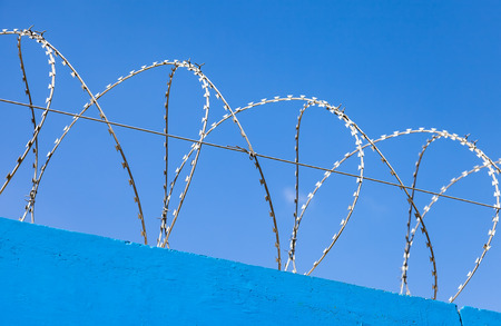 totalitarian: Barbed wire on the fence against a blue sky background