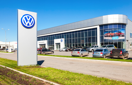 automaker: SAMARA, RUSSIA - MAY 14, 2016: Dealership sign and cars parked up near the office building of official dealer Volkswagen. Volkswagen Group is the biggest German automaker