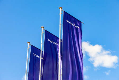 automaker: ST.PETERSBURG, RUSSIA - AUGUST 5, 2015: Volvo dealership flags over blue sky. Volvo is a Swedish multinational automaker company