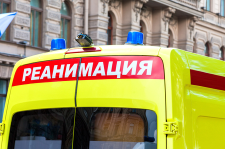 reanimation: Ambulance car with Blue Flashing Light on the roof. Text in russian: Reanimation