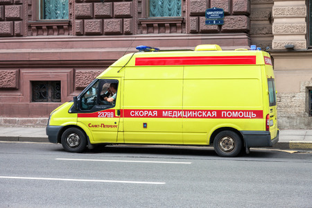ST. PETERSBURG, RUSSIA - JULY 31, 2016: Emergency ambulance car with blue flashing light on the roof parked up on the city street. Text in russian:  Ambulance, Reanimation