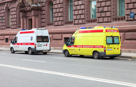 ST. PETERSBURG, RUSSIA - JULY 31, 2016: Emergency ambulance cars with blue flashing light on the roof parked up on the city street. Text in russian:  Ambulance, Reanimation Editorial