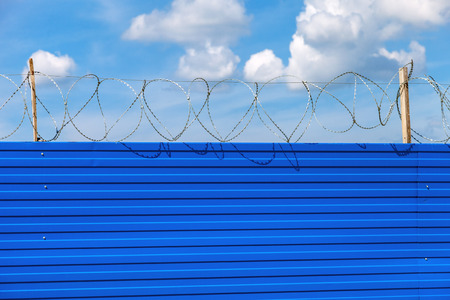 Barbed wire on the fence against a blue sky background. Restricted area Stock Photo