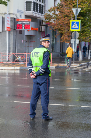 regulate: SAMARA, RUSSIA - SEPTEMBER 10, 2016: Russian police patrol officer of the State Automobile Inspectorate regulate traffic on sity street